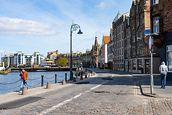 Leith, Edinburgh, Scotland, UK. 7 April 2020. In the third week of the nationwide coronavirus lockdown life in Leith continues although the streets are mostly deserted and shops closed. Pictured; Normally busy, The Shore in Leith is almost empty of people.