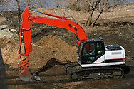 A tracked backhoe rests at a construction site on the south side of Chicago.