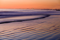 Dusk on the Pacific Ocean at Newport Beach with the coast of southern California in the background.