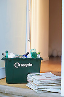 Recycling container and pile of waste paper on floor