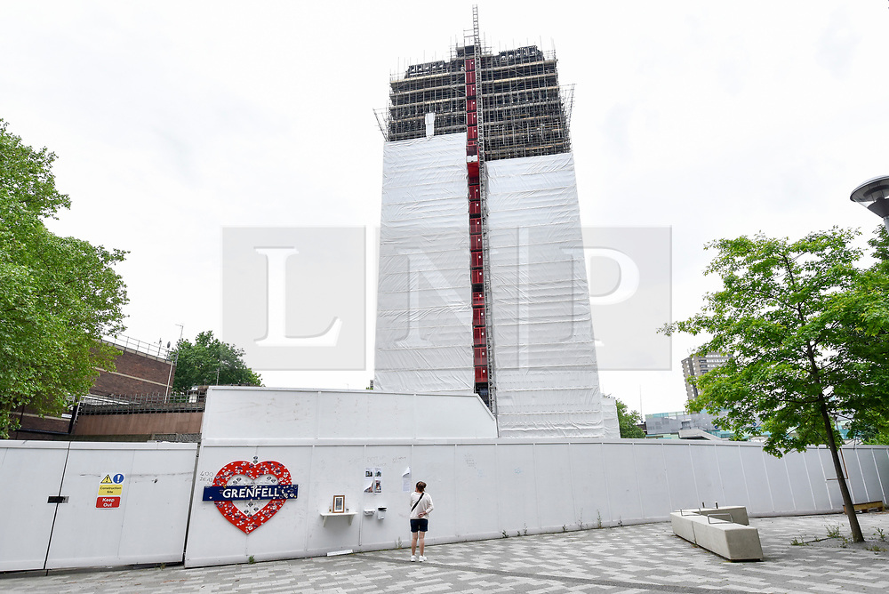 © Licensed to London News Pictures. 21/05/2018. LONDON, UK.  A member of the public looks at messages on a hoarding decorated with a memorial heart to the victims of the Grenfell Tower fire tragedy.  Behind the hoarding, scaffolding currently covers the burned out shell of the Grenfell Tower in West London on the day that commemoration hearings begin in the Millennium Gloucester hotel.  Over the next nine days, friends and family will be paying tributes to the 72 victims killed by the fire in the building nearly one year ago.  Photo credit: Stephen Chung/LNP