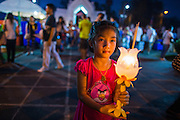 "25 FEBRUARY 2013 - BANGKOK, THAILAND:  A girl with a lantern joins a procession around Wat Benchamabophit Dusitvanaram (popularly known as either Wat Bencha or the Marble Temple) on Makha Bucha Day. Thais visit temples throughout the Kingdom on Makha Bucha Day to make merit and participate in candle light processions around the temples. Makha Bucha is a Buddhist holiday celebrated in Myanmar (Burma), Thailand, Cambodia and Laos on the full moon day of the third lunar month (February 25 in 2013). The third lunar month is known in Thai is Makha. Bucha is a Thai word meaning ""to venerate"" or ""to honor"". Makha Bucha Day is for the veneration of Buddha and his teachings on the full moon day of the third lunar month. Makha Bucha Day marks the day that 1,250 Arahata spontaneously came to see the Buddha. The Buddha in turn laid down the principles his teachings. In Thailand, this teaching has been dubbed the 'Heart of Buddhism'.     PHOTO BY JACK KURTZ"