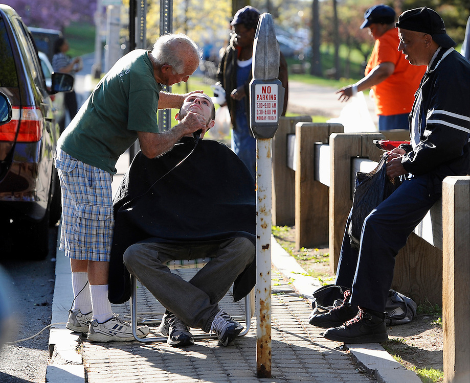Cymerys moves his alfresco shop next to his vehicle in order to power up his clippers after the portable car battery he was using died.  Client Aaron Peck of Hartford receives a haircut from Cymerys  at the new location between parking meters, in Hartford, Conn., Wednesday, May 1, 2013.