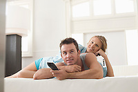 Young couple lying on bed and watching TV