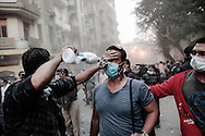 A protester receives a spray to relieve effects from tear gas on Mohamed Mahmoud street near Tahrir Square during clashes with riot police on November 22, 2011 in Cairo, Egypt.