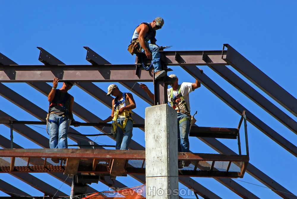 Steel Workers complete the metal roof structure of an office building in Austin Texas, July 21 2008. Steelworkers work in teams to fabricate, assemble, erect, position and join structural members of steel buildings.
