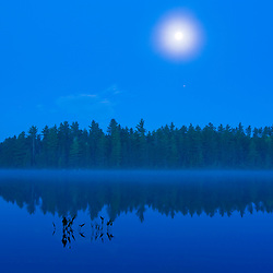 The moon sets over Long Pond in Errol, New Hampshire.