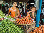 """25 OCTOBER 2015 - INSEIN, MYANMAR:  A child and his mother in a produce booth at Danyin Market (also known as Da Nyin) in Insein, Myanmar, about 90 minutes from Yangon. Vendors in the market sell just about everything people in the area need, but mostly it's a """"wet market"""" with fruits, vegetables and meats. Most people in Myanmar still do not have refrigerators in their homes, so people go to market almost every day.    PHOTO BY JACK KURTZ"""