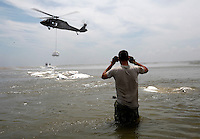U.S. Army National Guard troops work to build a barrier of giant sandbags against the BP oil spill offshore from Port Fourchon, Louisiana May 11, 2010. The troops were dropping sandbags with helicopters to fill in breaks in beaches to protect marshes.  REUTERS/Rick Wilking (UNITED STATES)