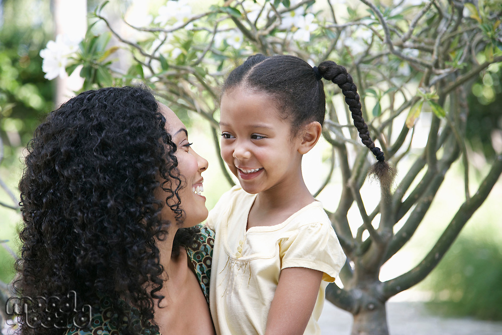 Mother and daughter (5-6 years) in garden