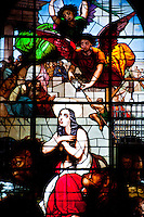 Milan, Italy, Duomo Cathedral. Stained glass window. Angels descending on a woman in a den of lions.