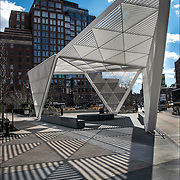 Shadows patterns and shapes from the sun directly above on the white canopy sculpture
