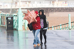 © Licensed to London News Pictures. 14/09/2015. Brighton, UK. Two woman are trying to shelter under an umbrella. Brighton and the South Coast is being battered by strong winds and powerful waves. Today September 14th 2015. Photo credit : Hugo Michiels/LNP