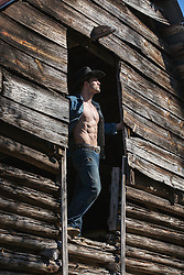 cowboy with a great body in a barn doorway on the upper level of a rustic barn