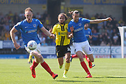 Burton Albion midfielder Marcus Harness (16) is held off by Portsmouth defender Christian Burgess (6) during the EFL Sky Bet League 1 match between Burton Albion and Portsmouth at the Pirelli Stadium, Burton upon Trent, England on 19 April 2019.