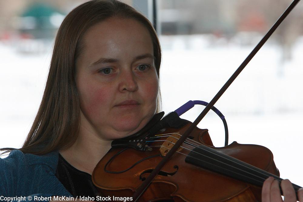 IDAHO. Boise. Jewish folk musician playing fiddle at Bat Mitzvah celebration. December 2008. #pa080701 MR