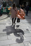 A lady carries two birthday 30th balloons along Bond Street in central London, on 6th April 2018, in London, England.