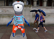 © Licensed to London News Pictures. 18/07/2012. London, UK People with umbrellas walk past an Olympic mascot statue on the Southbank of the Thames River. Rain in Central London today 18th July. Photo credit : Stephen Simpson/LNP