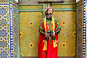 Fez, Morocco - 3rd FEBRUARY 2018 - Gnaoua musician wearing traditional dress performs infront of a colourful Moroccan doorway with zellige mosaic tiling, Fez Medina, Middle Atlas Mountains, Morocco.