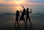 Portrait of young Thai children enjoying the last light of the day on Koh Lanta.