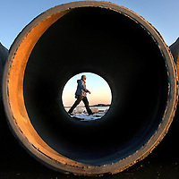 (01/24/06-So Boston,MA) The setting sun and construction pipes frame a walker on Pleasure Bay. Temps reached to near 40 degrees today. Photo by Mark Garfinkel