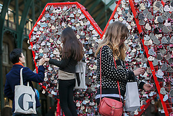 © licensed to London News Pictures. London, UK 14/02/2013. Couples adding their heart-shaped name tags on a heart-shaped fence to mark Valentine's Day in Covent Garden, London. Photo credit: Tolga Akmen/LNP