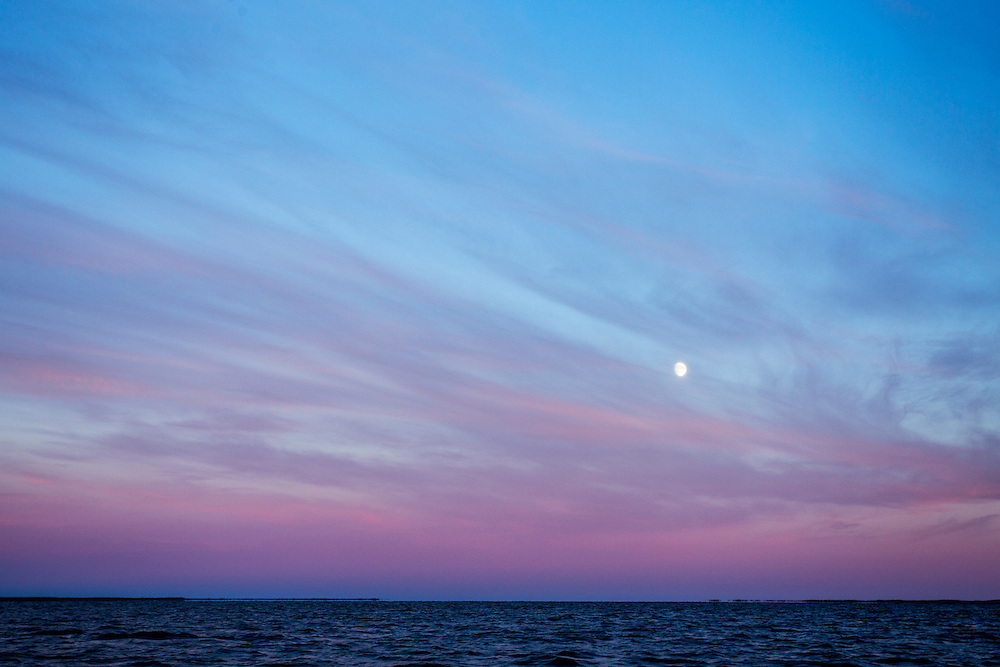 Canada, Manitoba, Gibbous moon rises through sunlit cirrus clouds above Hudson Bay near Churchill on summer evening