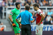 Referee Lee Probert checks on Petr Cech (#1) of Arsenal following a finger injury during the Premier League match between Newcastle United and Arsenal at St. James's Park, Newcastle, England on 15 September 2018.