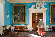 An actress playing a maid conducts a tour through the Governor's Palace on Duke of Gloucester Street in Colonial Williamsburg, Virginia, USA. Colonial Williamsburg is the historic district of the independent city of Williamsburg, which was colonial Virginia's capital from 1699 to 1780, and a center of education and culture.