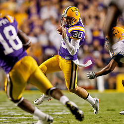 October 16, 2010; Baton Rouge, LA, USA; LSU Tigers punter Josh Jasper (30) runs a fake punt against the McNeese State Cowboys at Tiger Stadium. LSU defeated McNeese State 32-10. Mandatory Credit: Derick E. Hingle