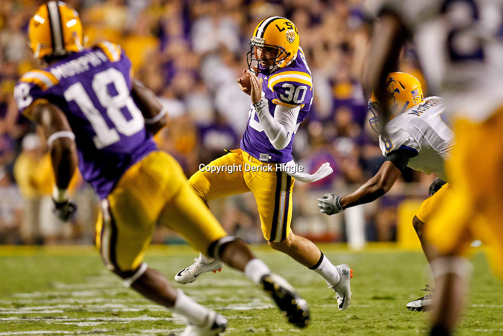 October 16, 2010; Baton Rouge, LA, USA; LSU Tigers punter Josh Jasper (30) runs a fake punt against the McNeese State Cowboys at Tiger Stadium. LSU defeated McNeese State 32-10. Mandatory Credit: Derick E. Hingle