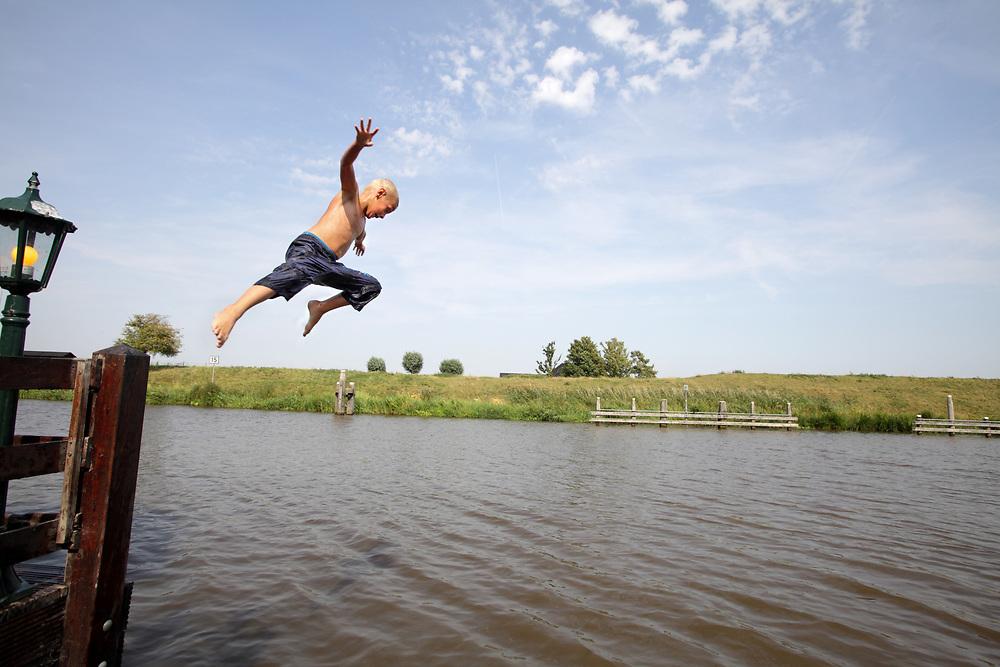 A boy jumps into the Reitdiep river in Garnwerd, Groningen province // Een jongen zoekt vanwege de hoge temperatuur (32 graden Celsius) verkoeling  door in het Reitdiep te springen.