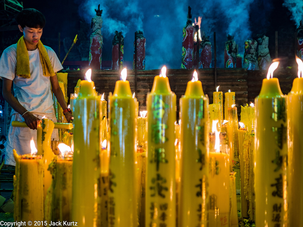 15 OCTOBER 2015 - BANGKOK, THAILAND:  A temple attendant keeps candles lit by devotees burning during the Vegetarian Festival at the Joe Sue Kung Shrine in the Talat Noi neighborhood of Bangkok. The Vegetarian Festival is celebrated throughout Thailand. It is the Thai version of the The Nine Emperor Gods Festival, a nine-day Taoist celebration beginning on the eve of 9th lunar month of the Chinese calendar. During a period of nine days, those who are participating in the festival dress all in white and abstain from eating meat, poultry, seafood, and dairy products. Vendors and proprietors of restaurants indicate that vegetarian food is for sale by putting a yellow flag out with Thai characters for meatless written on it in red.   PHOTO BY JACK KURTZ