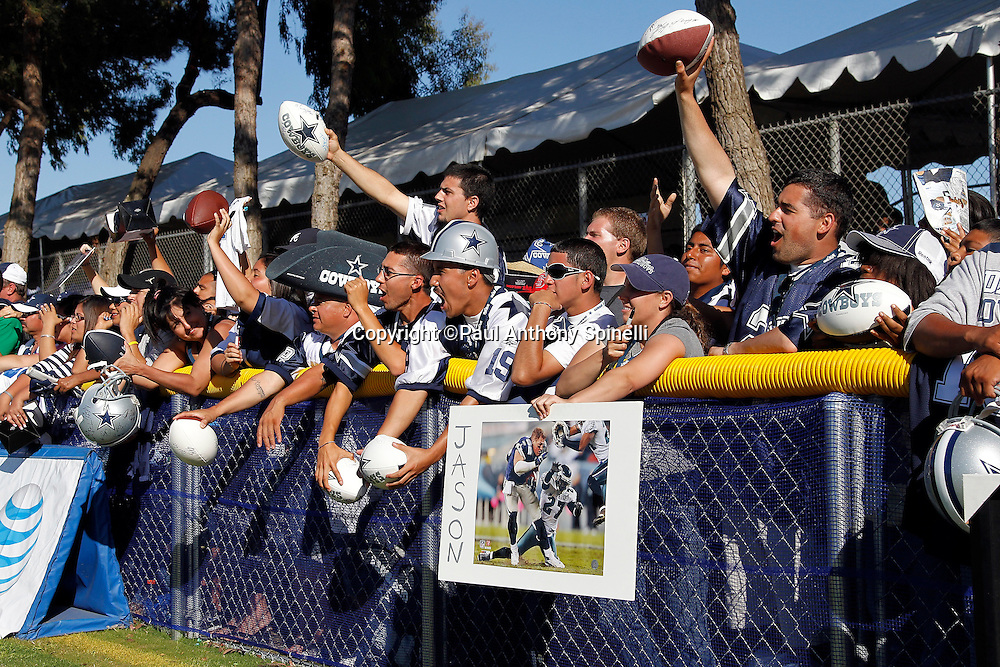 Fans cheer and hold up autograph items as the Dallas Cowboys finish NFL football training camp on Wednesday, August 18, 2010 in Oxnard, California. (©Paul Anthony Spinelli)