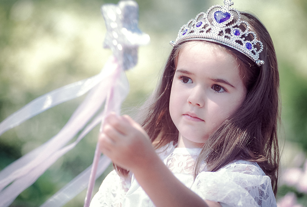 Young girl in princess costume examines majic wand with colorful streamers.