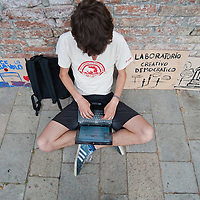 """VENICE, ITALY - MAY 27:  A supporter of the Spanish movement  """"Democracia Real Ya"""" keep in contact using his laptop with Spanish protesters using a social network on May 27, 2011 in Venice, Italy. The protest takes place on the day when Spanish police fired rubber bullets to disperse anti-crisis protesters in a Barcelona square as cleaning crews cleared their tent camp."""