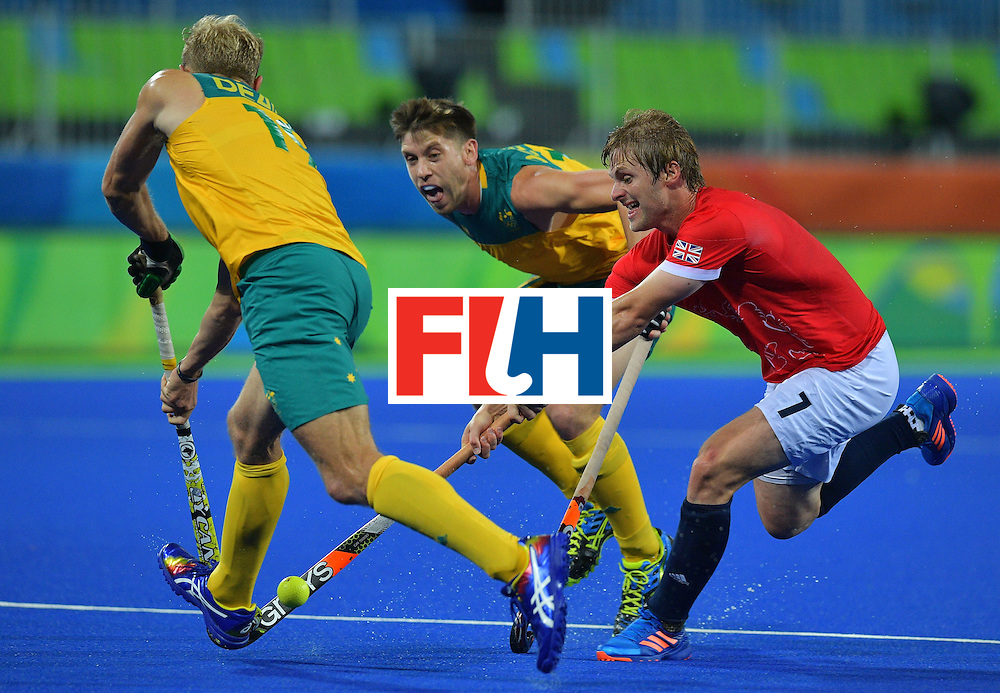 Britain's Ashley Jackson (R) tries to get past Australia's Tim Deavin (L) and Australia's Eddie Ockenden during the men's field hockey Britain vs Australia match of the Rio 2016 Olympics Games at the Olympic Hockey Centre in Rio de Janeiro on August, 10 2016. / AFP / Carl DE SOUZA        (Photo credit should read CARL DE SOUZA/AFP/Getty Images)