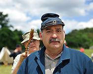 Old Bethpage, New York, USA - July 21, 2012: GENE MONGELLO of Levittown, stands at front in uniform, while behind him, visitor PETER C. FALES of Bayshore, NY, points his cane forward to show how a file closer soldier makes sure there are no empty places in a line file of soldiers during battle, at recreation of Camp Scott, a Union Army training camp, is portrayed by Federal Re-enactors at Old Bethpage Village Restoration, to commemorate 150th Anniversary of American Civil War, on Saturday, July 21, 2012.