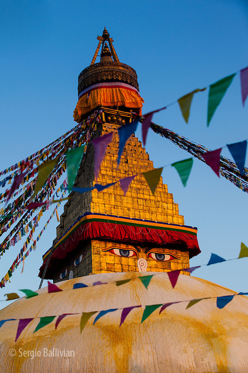 The last rays of sunshine light the ever seeing eyes and prayer flags at the Boudhanath Stupa in Kathmandu, Nepal.