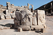 Large round monument carved with bull's heads and garlands, Domitian Square, with the arch of the Fountain of Pollio in the centre distance and the Temple of Domitian on the right, Ephesus, Izmir, Turkey. The monument was moved here in the 4th century AD. Ephesus was an ancient Greek city founded in the 10th century BC, and later a major Roman city, on the Ionian coast near present day Selcuk. Picture by Manuel Cohen