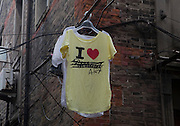 A t-shirt out to dry on the clothes line in a working class Chinese neighborhood.