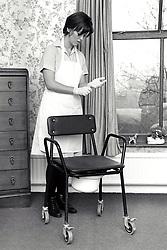 Carer cleaning resident's comode, residential home for the elderly, Nottingham UK 1995