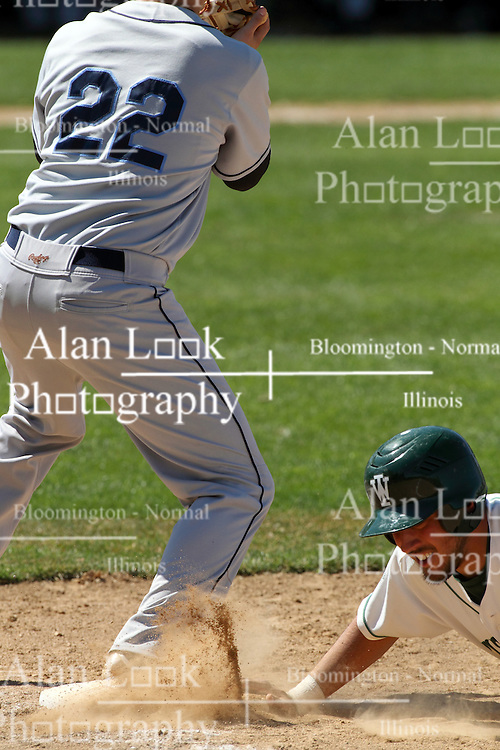 14 April 2013:  Anthony Lopez dives back to first on a pick off attempt to Luke Collins during an NCAA division 3 College Conference of Illinois and Wisconsin (CCIW) Baseball game between the Elmhurst Bluejays and the Illinois Wesleyan Titans in Jack Horenberger Stadium, Bloomington IL
