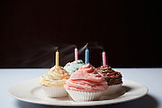 Colourful cupcakes with blowed birthday candles on plate
