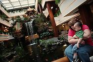 Aupres de la celebre cascade interieure de l'hotel White Swan a Canton, Deby tient dans ses bras son fils adoptif Nicolas (11 mois).