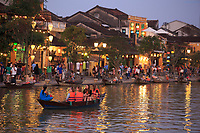 Tourists enjoy a river cruise beside Bach Dang Street in the old town of Hoi An, Vietnam