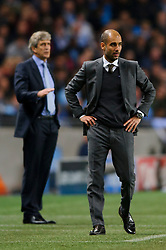 Bayern Manager Josep Guardiola (ESP) looks on sternly  with Man City Manager Manuel Pellegrini (CHI) behind during the second half of the match - Photo mandatory by-line: Rogan Thomson/JMP - Tel: Mobile: 07966 386802 - 02/10/2013 - SPORT - FOOTBALL - Etihad Stadium, Manchester - Manchester City v Bayern Munich - UEFA Champions League Group D.