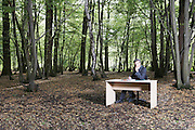 Business man sitting at desk in middle of forest