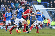 Barnsley Forward, Cauley Woodrow (9) runs at Portsmouth Defender, Matt Clarke (5) and Portsmouth Midfielder, Tom Naylor (7) during the EFL Sky Bet League 1 match between Portsmouth and Barnsley at Fratton Park, Portsmouth, England on 23 February 2019.