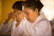 "10 MARCH 2006 - TAY NINH, VIETNAM: Women pray at the Cao Dai temple in Tay Ninh. The Cao Dai complex in Tay Ninh is the sect's headquarters. The Cao Dai religion is a blending of Buddhism, Confucianism, Taoism, Christianity and Islam. There ""saints""  include Chinese leader Sun Yat Sen and French author Victor Hugo. There are about two million members of the Cao Dai religion in Vietnam. British author Graham Greene, who wrote about the Cao Dai in the ""The Quiet American"" said the relegion was ""a Walt Disney fantasia of the East."" Photo by Jack Kurtz / ZUMA Press"